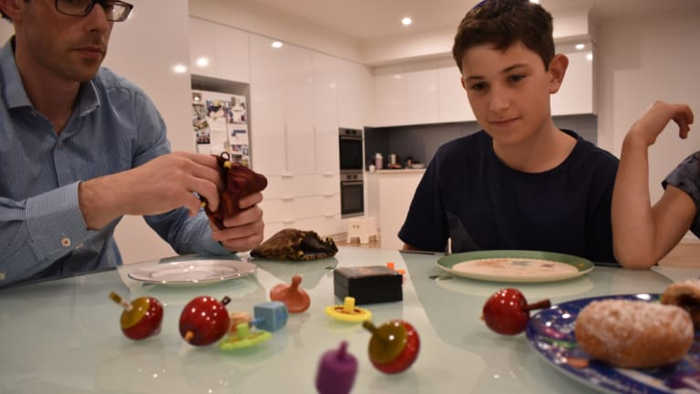 Benjamin looks on towards his mum, Kirsten's dreidel to see whether she'll get to take a chocolate money or have nothing at all.