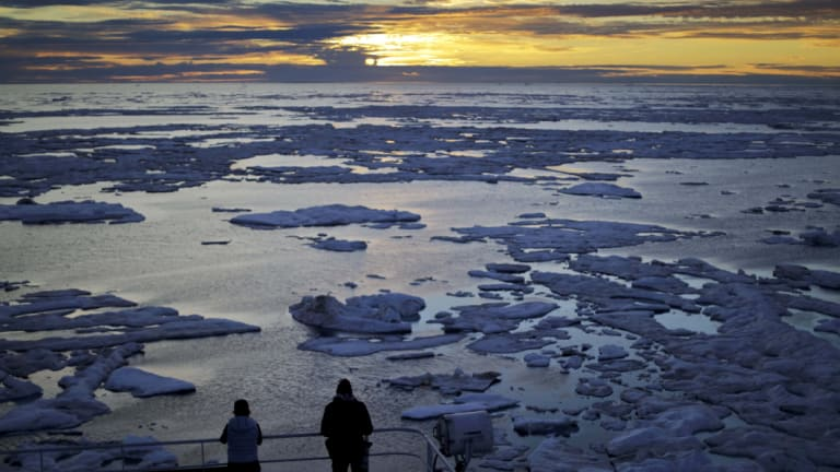 Researchers look out over sea ice in the Victoria Strait along the Northwest Passage in July last year.