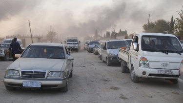 Syrians flee shelling by Turkish forces in Ras al Ayn, north-east Syria.