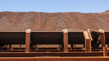 An ore conveyor belt in front of an iron ore stockpile at BHP's Jimblebar facility in the Pilbara.