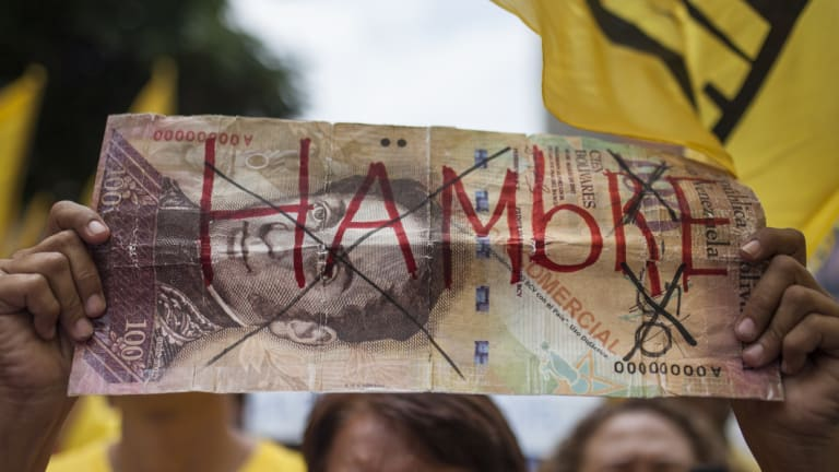 """A protester in Venezuela holds a fake banknote with the word """"Hungry"""" written on it in 2016."""