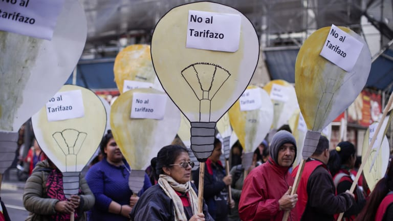"People hold cutouts of light bulbs with words that read in Spanish ""no to the price hike"" on Wednesday in Buenos Aires."