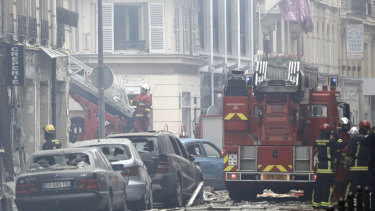 Firefighters work at the scene of a gas leak explosion in Paris