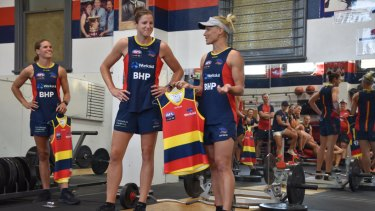 Jess Foley (centre) is presented with her Adelaide Crows jumper by teammate Erin Phillips (right).