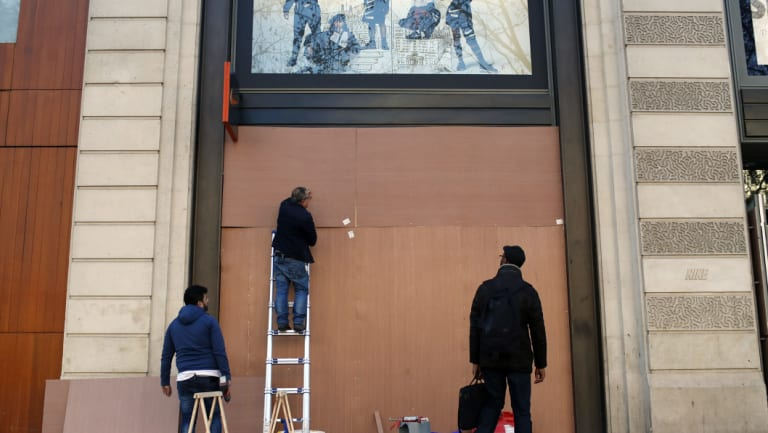 """Workers reinforce store windows on the Champs-Elysees to prepare for an expected protest by the """"yellow jackets""""."""