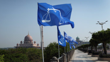 Campaign flags for the Barisan Nasional party fly as the Putra Mosque, left, stands in the background in Putrajaya, Malaysia, on Friday.