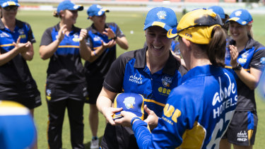 Anna Lanning is presented with her ACT Meteors cap by captain Erin Osborne.