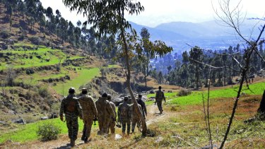 Pakistani soldiers patrol in the area where Indian planes were reportedly shot down by Pakistani forces.