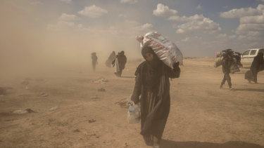 A woman carries supplies from a reception area for people evacuated from the last shred of territory held by Islamic State militants, outside Baghouz, Syria.