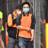 Construction workers in face masks leave a city building site earlier this week.