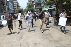 Protesters run to avoid security forces in Yangon.