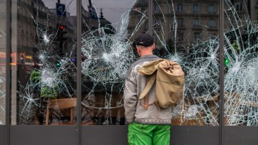 A person looks at shattered windows on a Starbucks Corp. cafe during the yellow vests (Gilets jaunes) protests in Paris on Saturday.