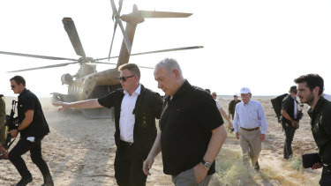 Israeli Prime Minister Benjamin Netanyahu, centre, and then US National Security Advisor John Bolton, back right, come out of a military helicopter after a flight in the Jordan Valley between the Israeli city of Beit Shean and the Palestinian city of Jericho, West Bank, in June.