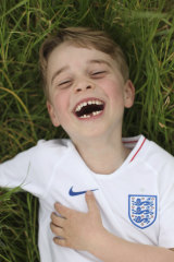 Prince George laughs and frolics on a bed of grass.