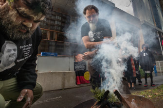 Raymond Noel's father, Raymond Thomas, takes part in a smoking ceremony outside the coroners court during an inquest into his death.