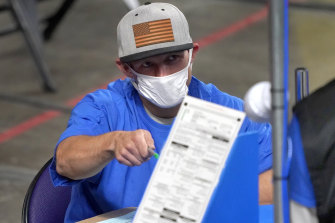 Maricopa County ballots cast in the 2020 general election are examined and recounted by contractors in Phoenix.