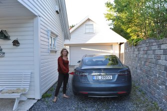 Norwegians have the highest uptake of EVs. Here, a resident charges her Tesla electric car.