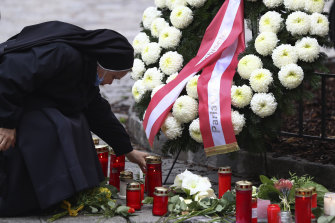 A nun lights a candle at the scene of Monday's terror attack in central Vienna.
