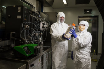 Professor George Lovrecz and Mylinh La at CSIRO's vaccine manufacturing plant in Clayton. They hold a bottle filled with cells that will be used to produce protein for the vaccine. Behind them is a machine that will eventually be used to purify the vaccine.