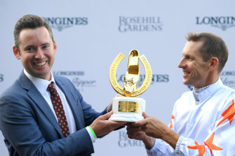 Hugh Bowman holds the Golden Slipper trophy with co-trainer Adrian Bott after Farnan's win on Saturday