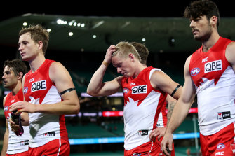 The dejected Swans trudge off after their narrow loss to Essendon at the SCG on Sunday.