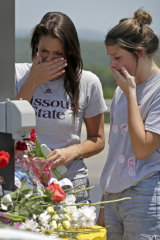 Rina Bernard, left, and Keri Johnson leave flowers on a car believed to belong to a victim of the duck boat accident.