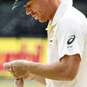 David Warner applies a bandage to his injured hand on the third day of the second Test in Port Elizabeth.