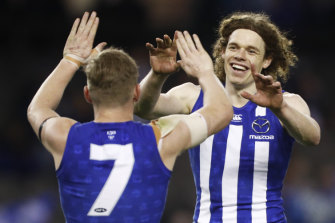 Ben Brown of the Kangaroos (right) celebrates one of his 10 (yes,10) goals in North's drubbing of Port Adelaide.