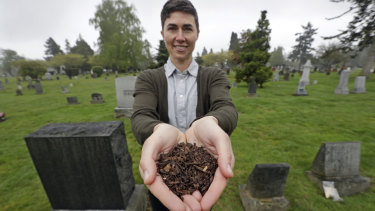 Katrina Spade, the founder and chief executive of Recompose, displays a sample of the compost material left from the decomposition of a cow, using a combination of wood chips, alfalfa and straw, as she poses in a cemetery in Seattle.