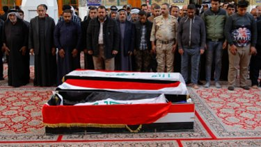 Mourners pray over the flag-draped coffins of three bombing victims in Najaf, on Monday.