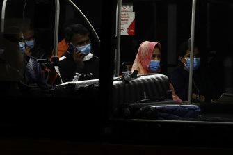 Returning travelers catch the Skybus to hotel quarantine.