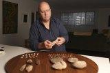 Institute of Aboriginal and Torres Strait Islander Studies chief executive Craig Ritchie with Indigenous stone tools.