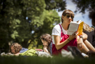 Molly George (right) enjoys some serious reading time in Carlton Gardens at the Silent Reading Party.