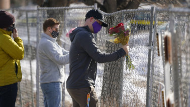 Kiefer Johnson places a bouquet of flowers into a makeshift fence put up around the parking lot outside a King Soopers grocery store where a mass shooting took place a day earlier, in Boulder, Colorado.