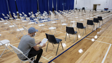 A man sits and waits after getting his first COVID-19 vaccine shot on the last day of the mass vaccination site at the University of North Georgia, Gainesville campus.