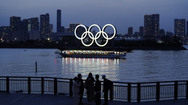 People watch illuminated Olympic rings floating in the waters off Odaiba island in Tokyo.