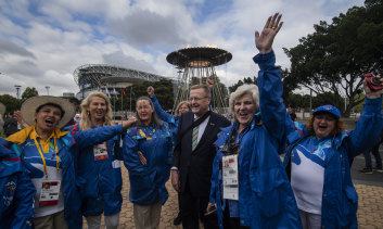 John Coates with Sydney 2000 volunteers at the re-lighting of the Olympic cauldron on Tuesday.