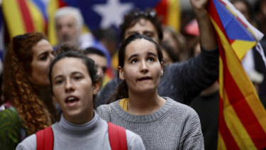 People holding Estelada pro Catalonia independence flags shout slogans during a protest in front of the Spanish embassy in Brussels.