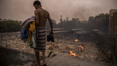 A man does his household chores against the backdrop of burning funeral pyres of the patients who died of the COVID-19 at a crematorium in Delhi.