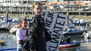 "Swedish teen climate activist Greta Thunberg carries the placard ""School strike for the climate"" which she held outside the Swedish parliament, upon her arrival in Santo Amaro Recreation dock in Lisbon."