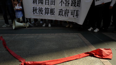 """Protesters carry a banner with Chinese reads """"Do not trample on press freedom"""" next to a red ribbon symbolising the bottom line of the Chinese Communist Party during a protest in Hong Kong."""