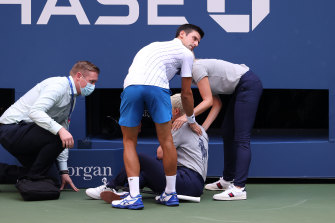Novak Djokovic tends to a line judge after she was struck by a frustrated strike from the US Open favourite.
