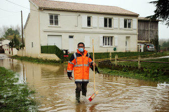 A volunteer on a flooded road in Coussan, near Marmande, south- western France. The worst flooding in 40 years swelled the Garonne River between Bordeaux and Toulouse in February turning orchards and vineyards into lakes.