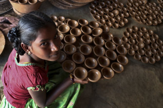 An Indian potter girl with earthen lamps for Diwali in Hyderabad, India.