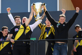 Trent Cotchin and Damien Hardwick lift the cup with Dustin Martin and Jack Riewoldt behind.