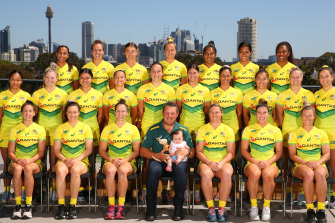 The Australian women's sevens team, with Emilee Cherry's daughter Alice sitting on the coach's knee.