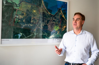 Mike Milliken of the Lyon Group in his office in front of a map of Boydtown.