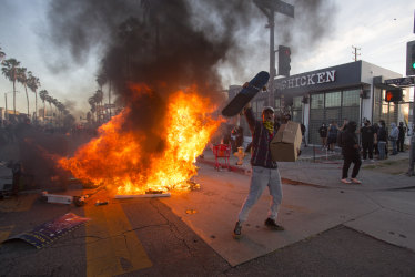 Clashes, looting and buildings torched: Protesters defy curfews across America