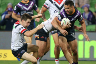 Head knock: Roosters five-eighth Luke Keary reels out of a tackle on Storm fullback Jahrome Hughes.