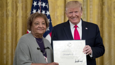 US President Donald Trump presents a Certificate of Commendation to Minnie Grant, the mother of Christopher Grant, one of five civilians celebrated for their heroism during a mass shooting in El Paso.  Grant was stopped by Secret Service from attending.